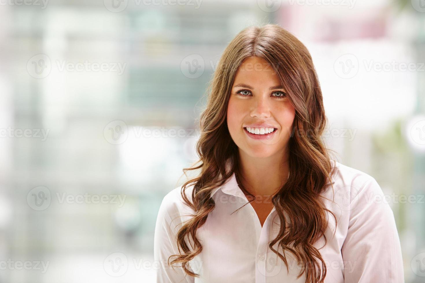 Head and shoulders portrait of a young businesswoman smiling photo
