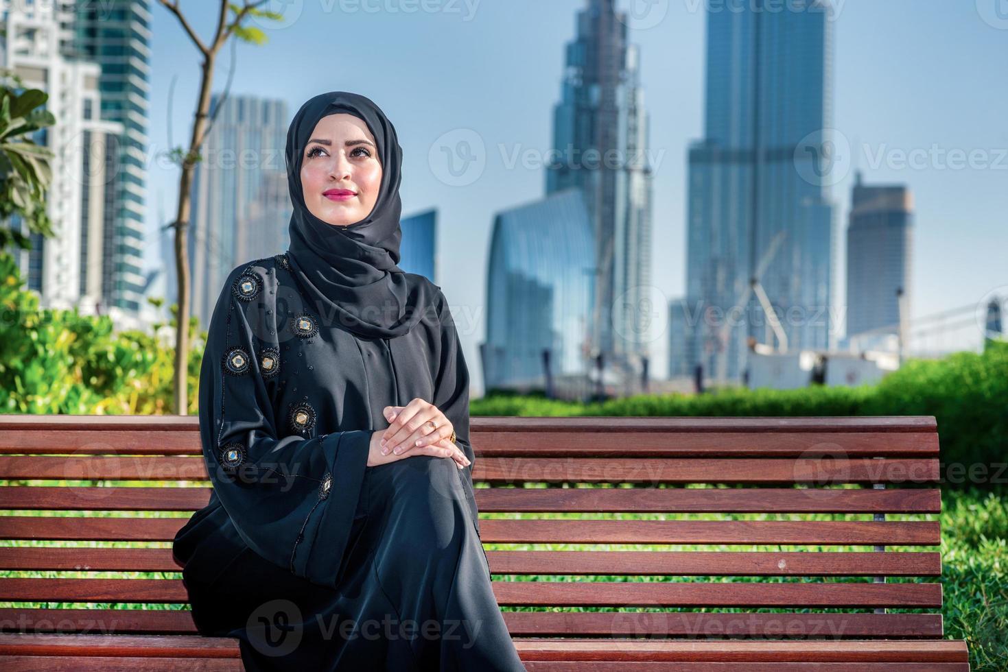 Éxito árabe. Empresarias árabes en hijab sentado en un banco foto