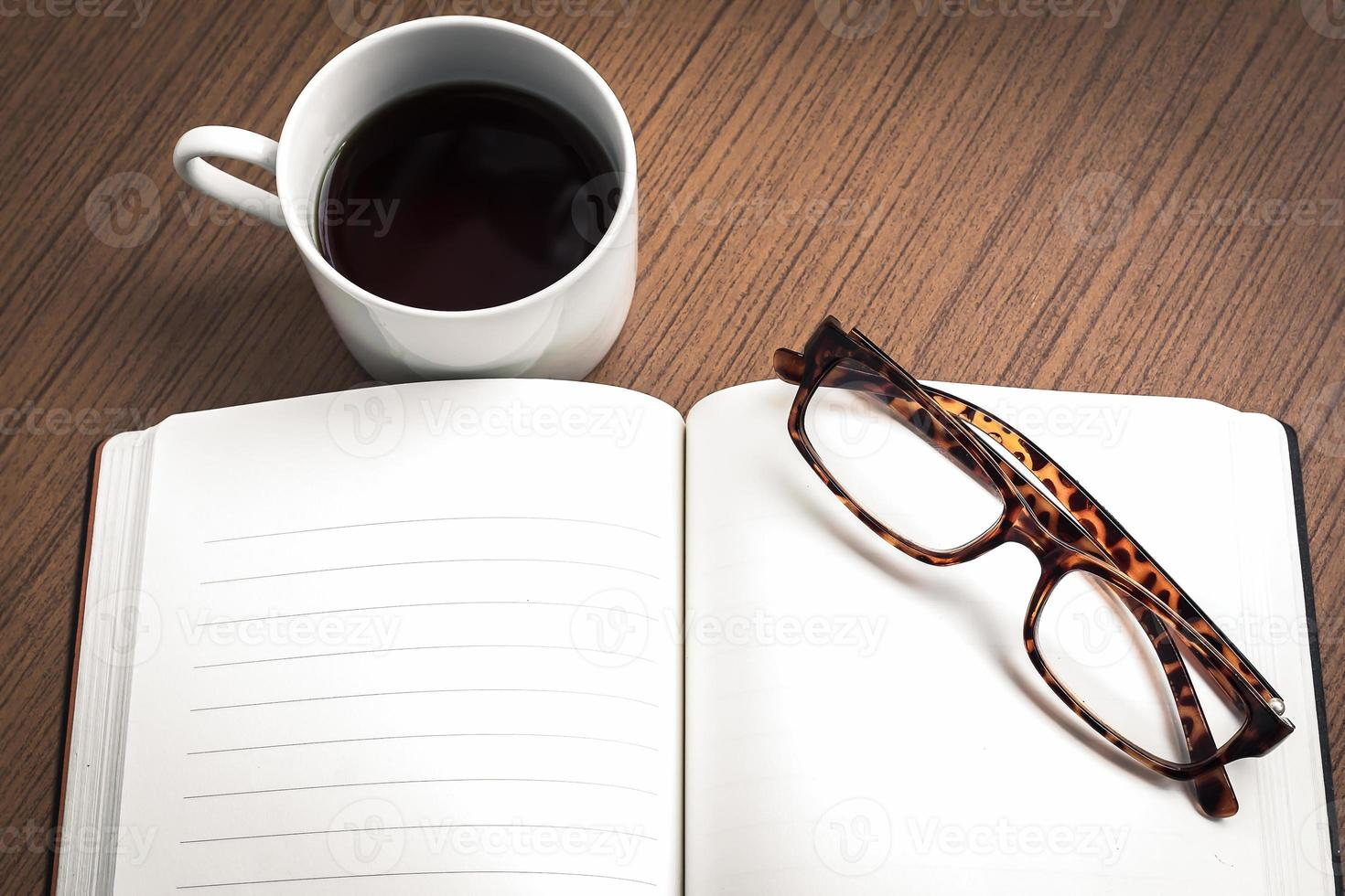 Eyeglasses on empty notebook and coffee over wood table photo