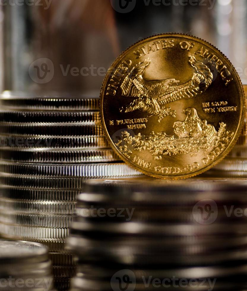US Gold Eagle rests among piles of silver coins photo