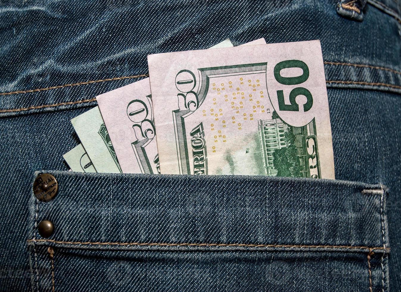 dólares estadounidenses en el bolsillo trasero de los jeans foto