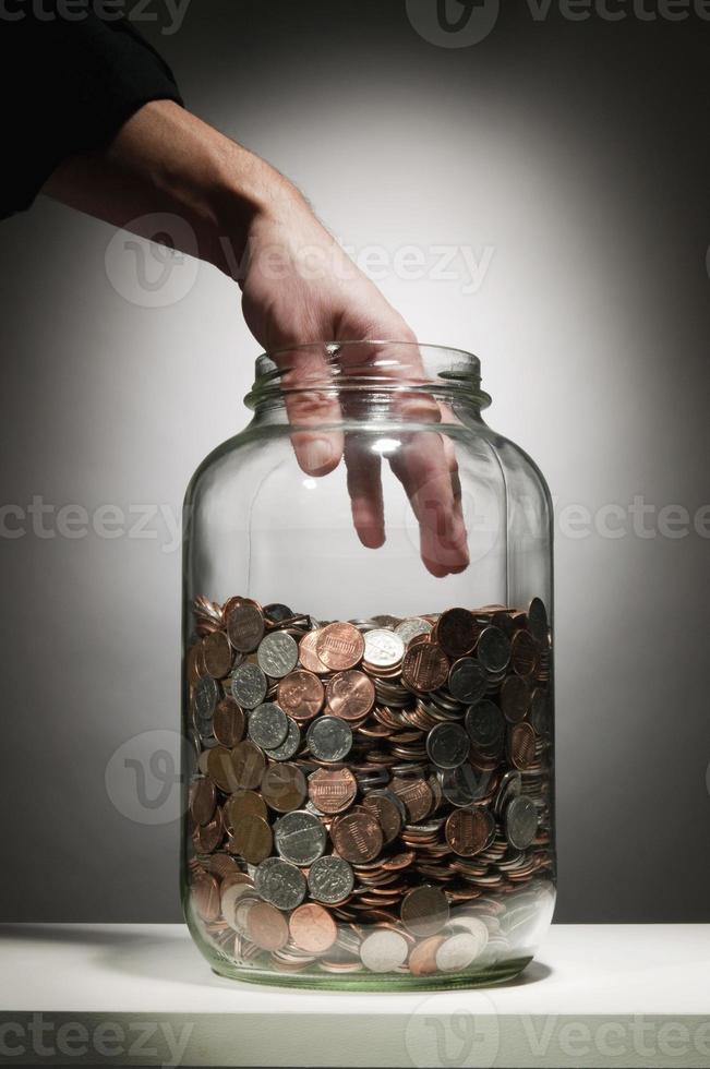 Hand reaching into jar of coins photo