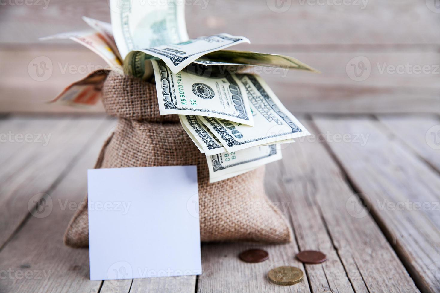money piece of burlap for notes on the wooden background photo
