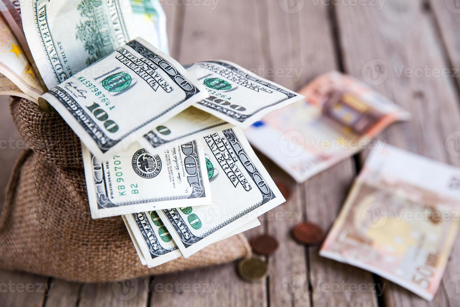 money in sackcloth and coins scattered on a wooden background photo