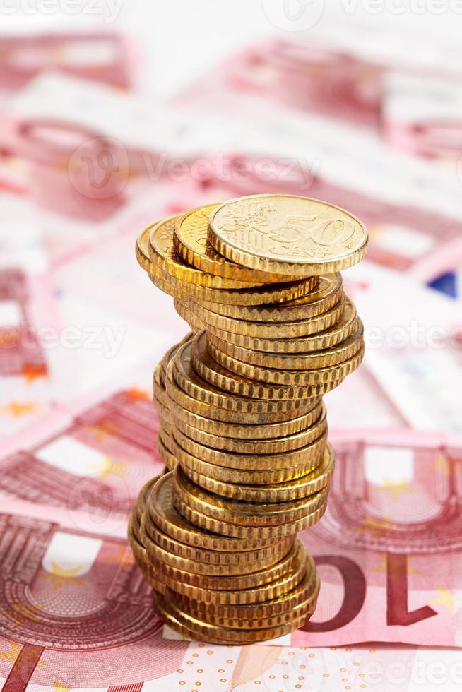 pila de monedas de euro en billetes de euro foto