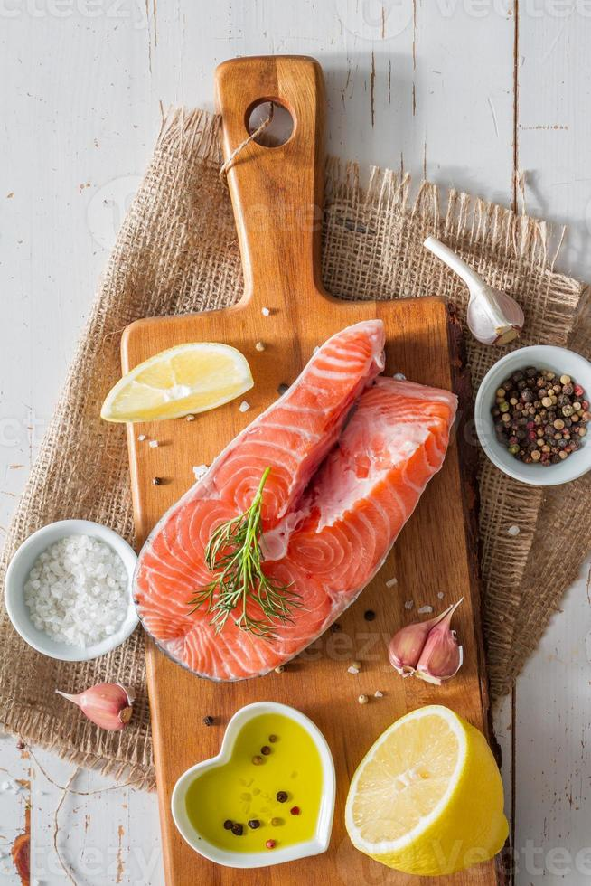 Salmon steak with lemon slices and spices photo