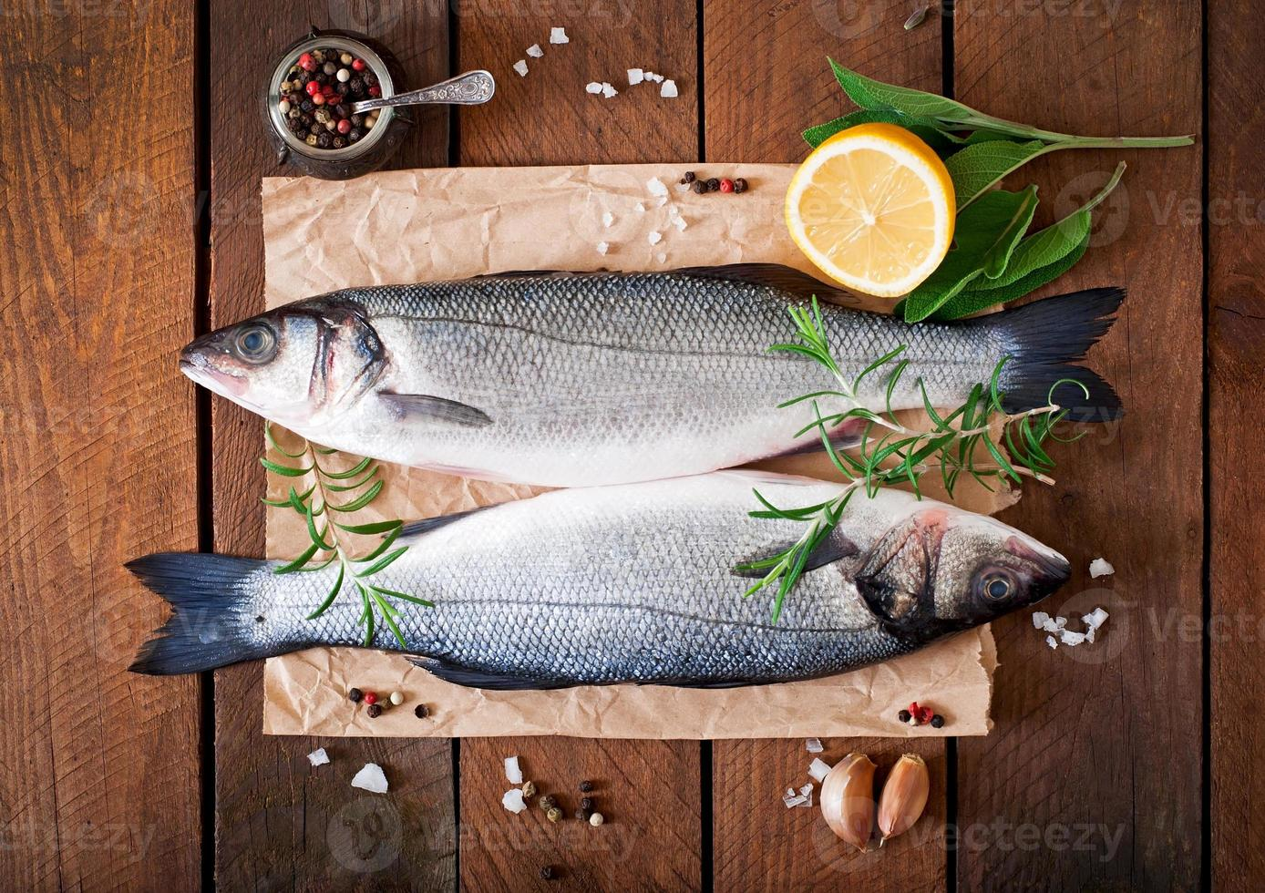 Two raw seabass with spices on an old wooden background. photo