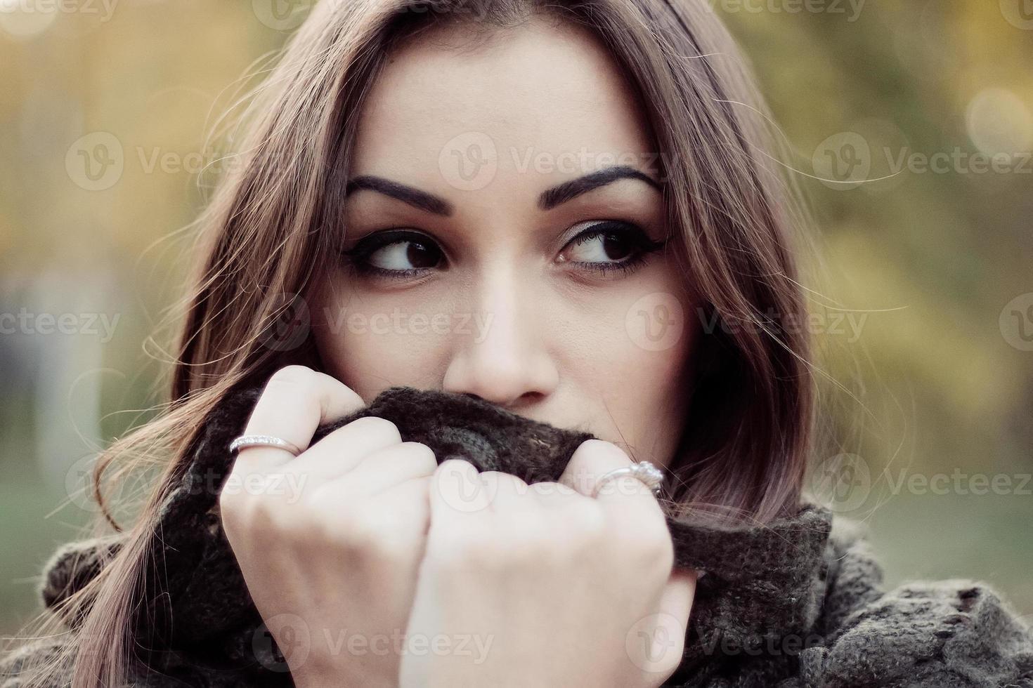 mujer triste de cabello oscuro envuelta en una bufanda foto