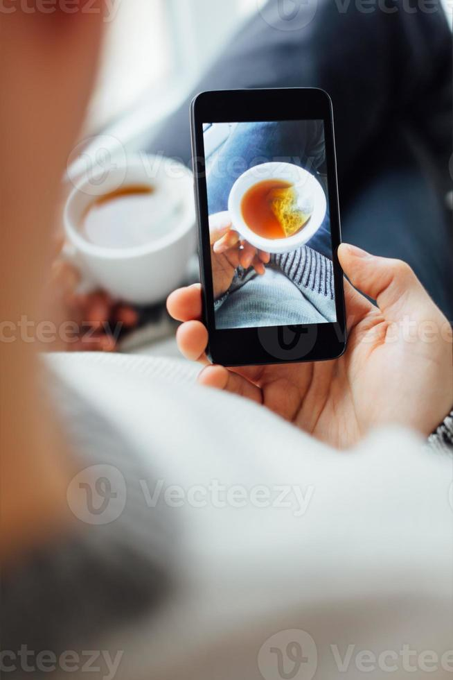Man taking self portrait with cup of tea photo