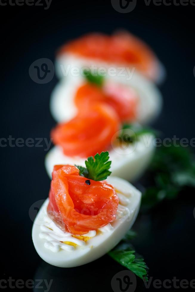 boiled egg with salty salmon on black background photo