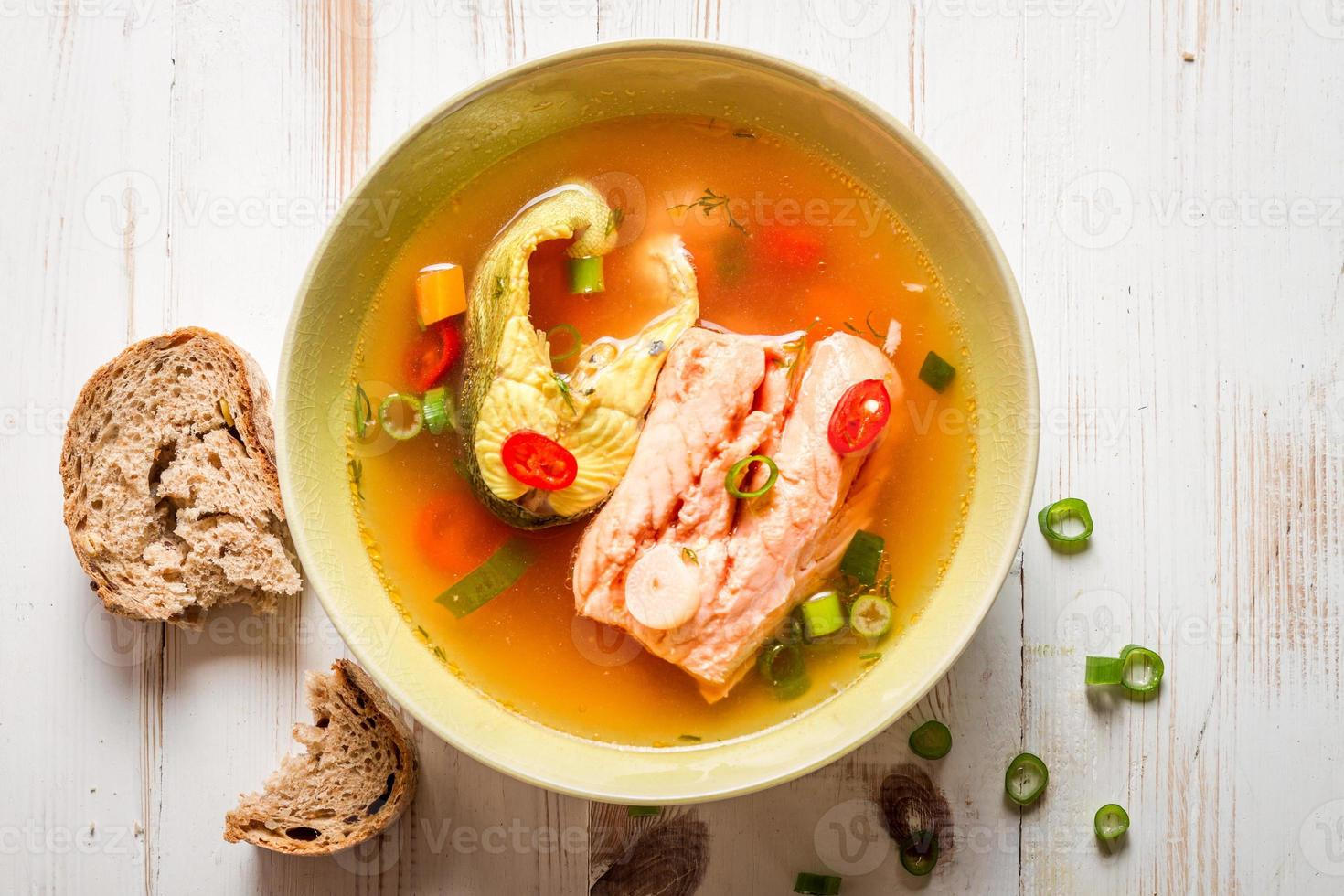 Salmon soup served with bread photo