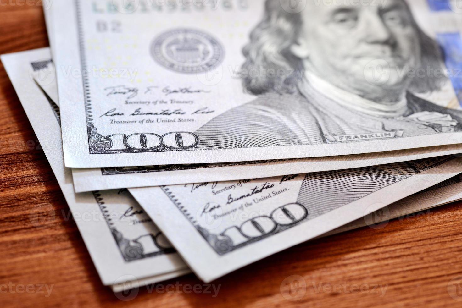 Billetes de dólares americanos en mesa de madera foto