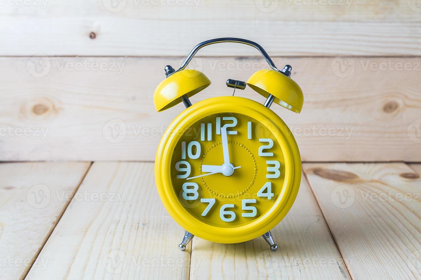 Yellow alarm clock on wood background photo