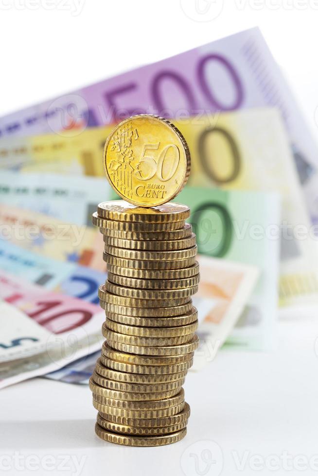 pilha de moedas de euro em notas de euro foto