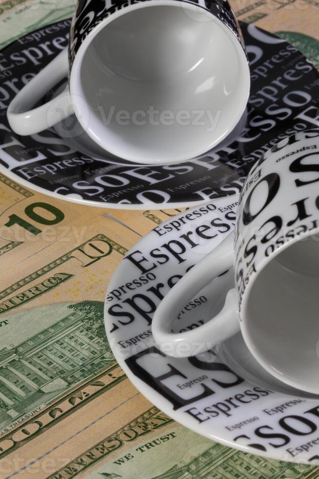 dos tazas de café vacías y billetes en dólares estadounidenses foto