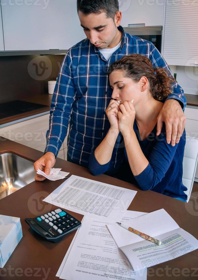 Unemployed husband gives solace to his wife crying by debts photo