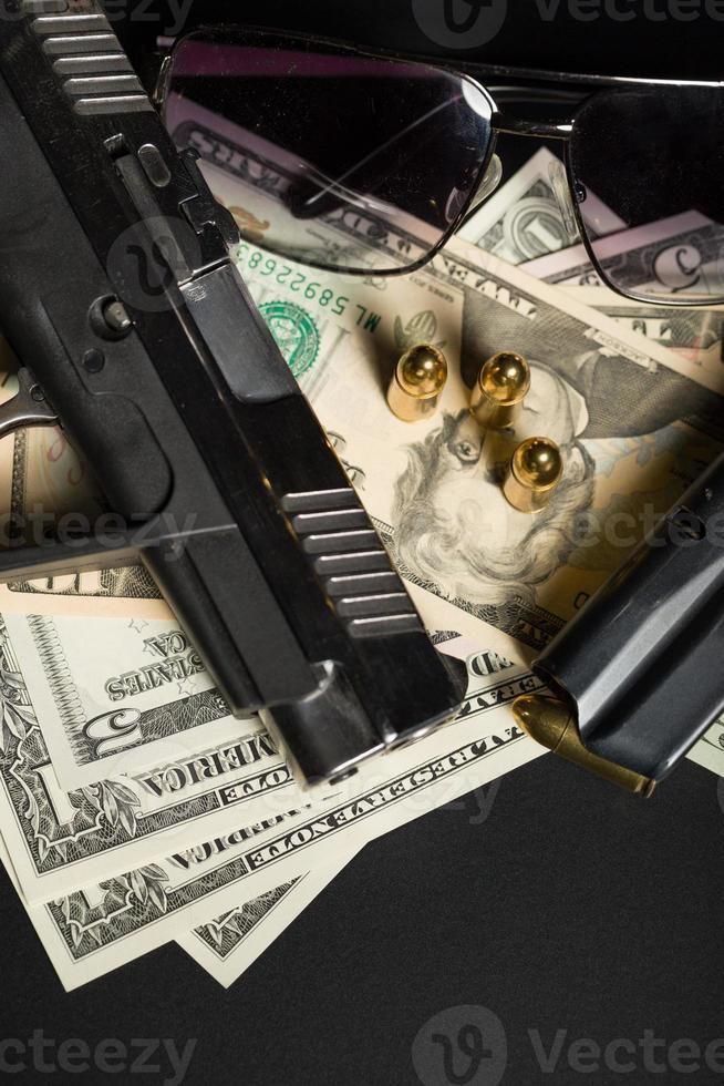 pistola con bala en billetes de dólar estadounidense foto