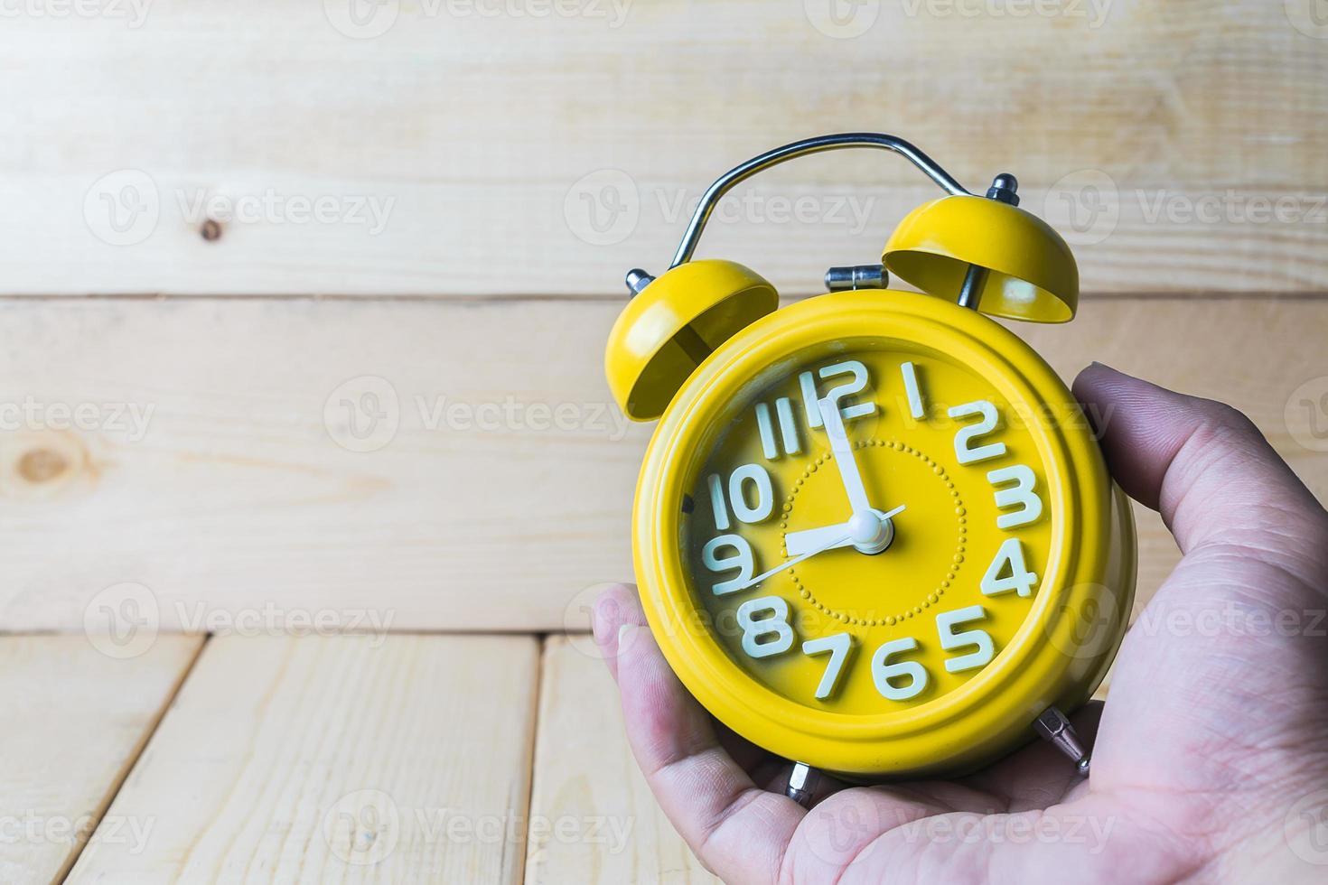 mano sostenga el despertador amarillo sobre fondo de madera foto
