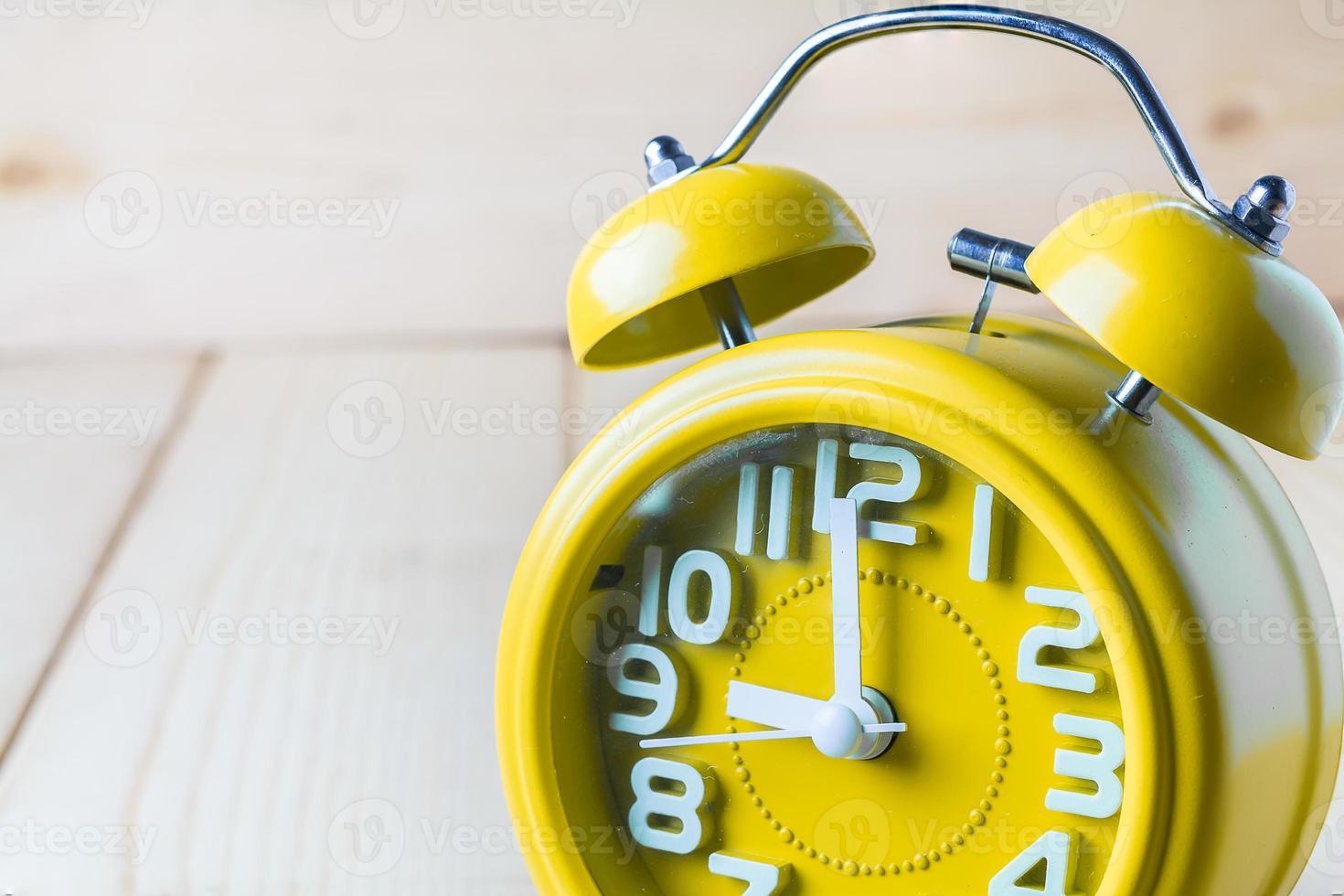 despertador amarillo sobre fondo de madera foto
