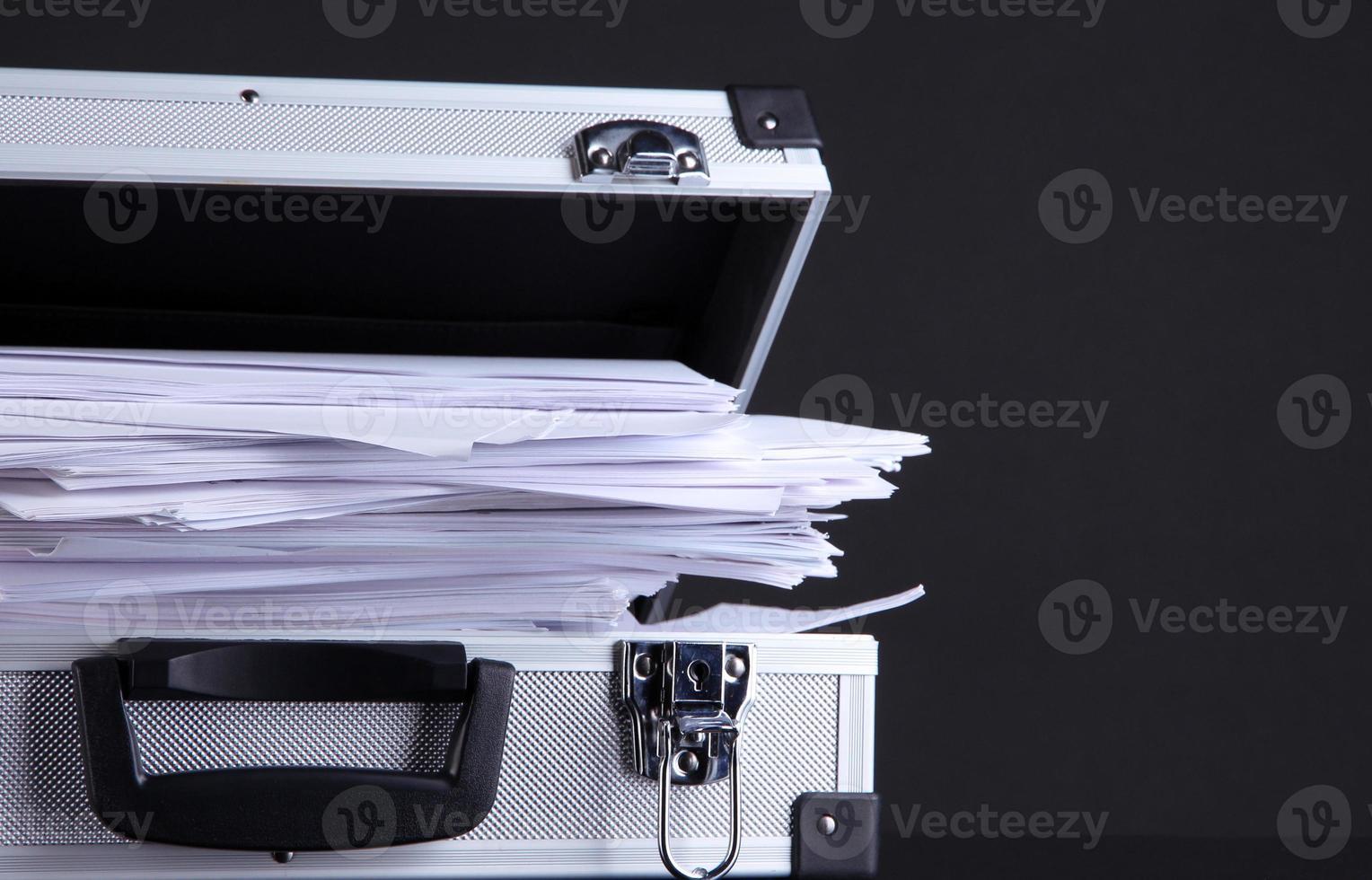 maletín lleno de papeles, aislado en negro foto