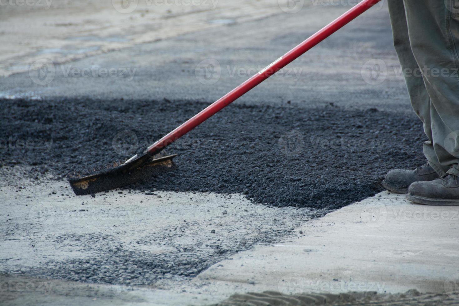 Worker raking asphalt photo