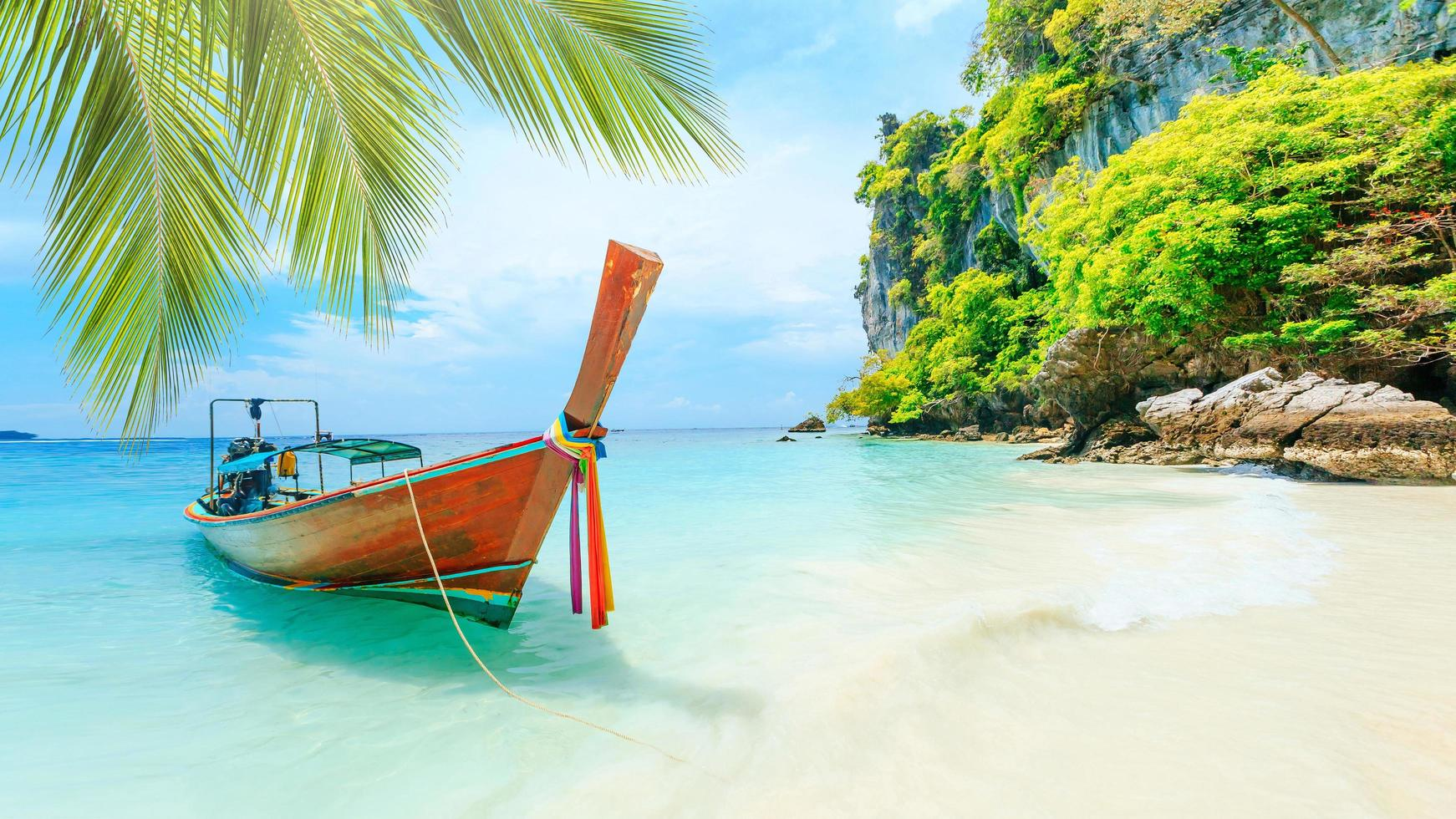 Long-tale boat on white beach in Phuket, Thailand photo