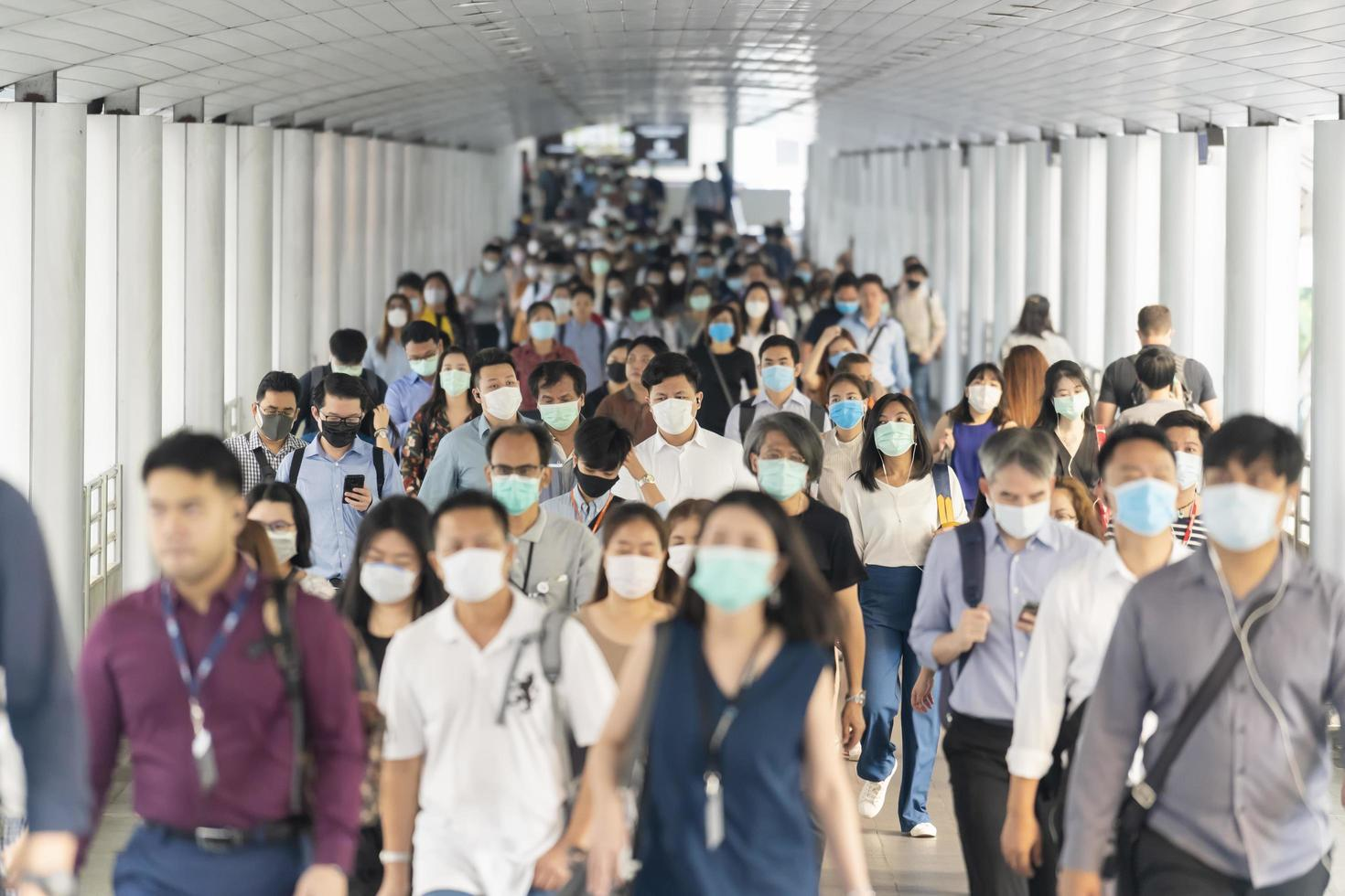 Bangkok, Thailand, March 2020, A crowd of unrecognizable business people wearing surgical mask to prevent coronavirus outbreak photo