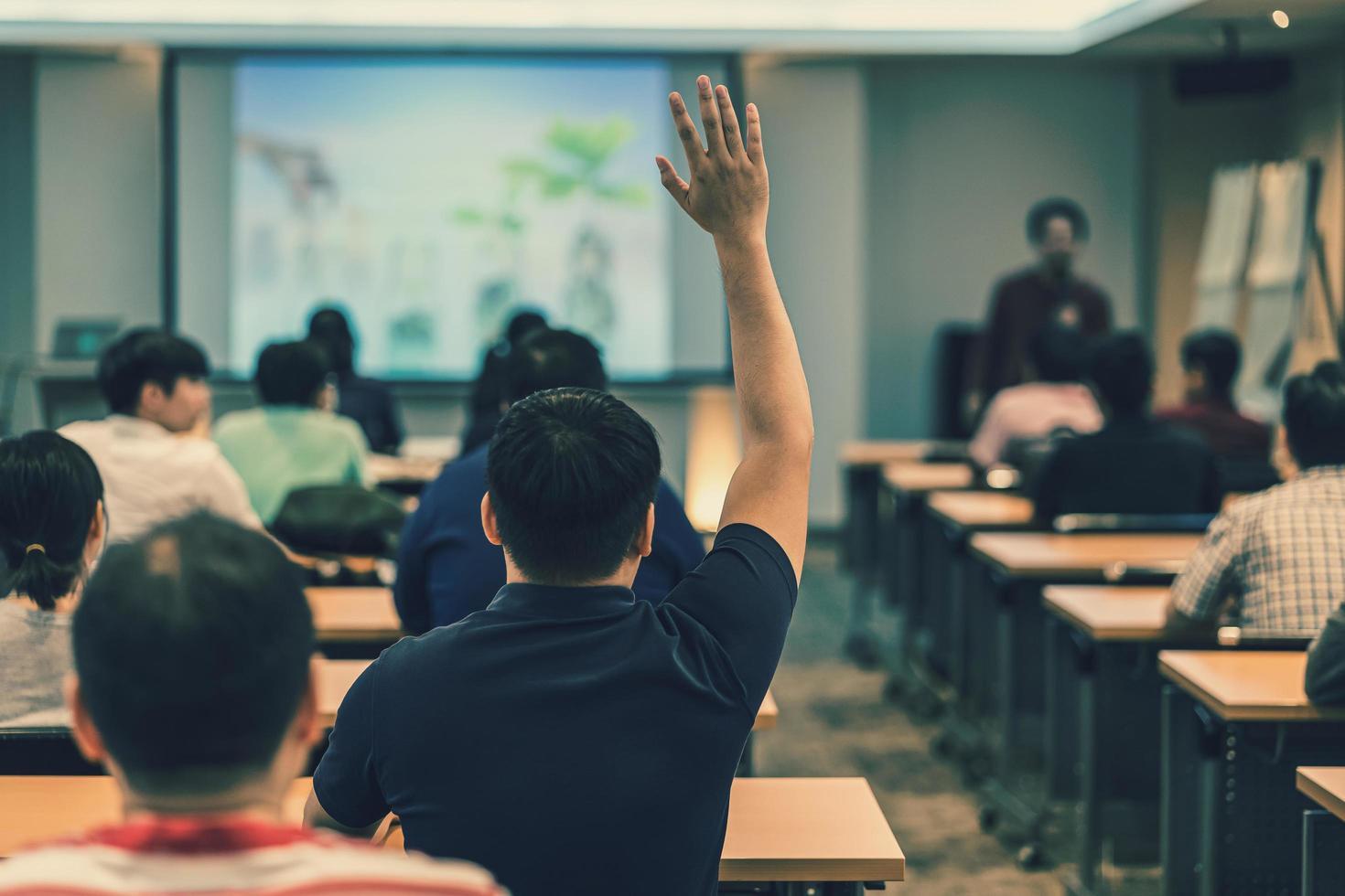 Un joven levanta la mano durante una conferencia en un taller foto