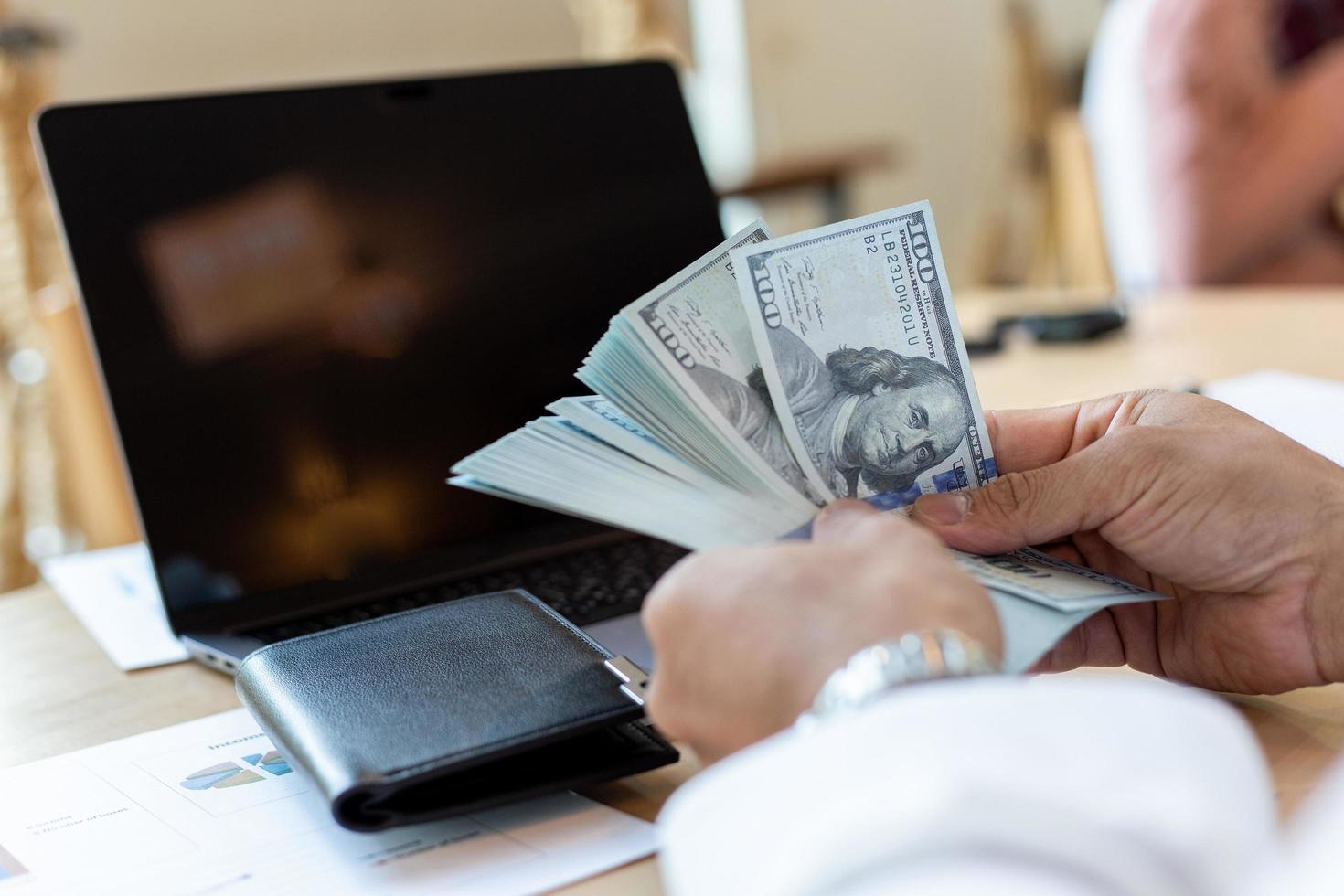 zakenman behandelt geld op het werk om financiële overzichten te analyseren foto