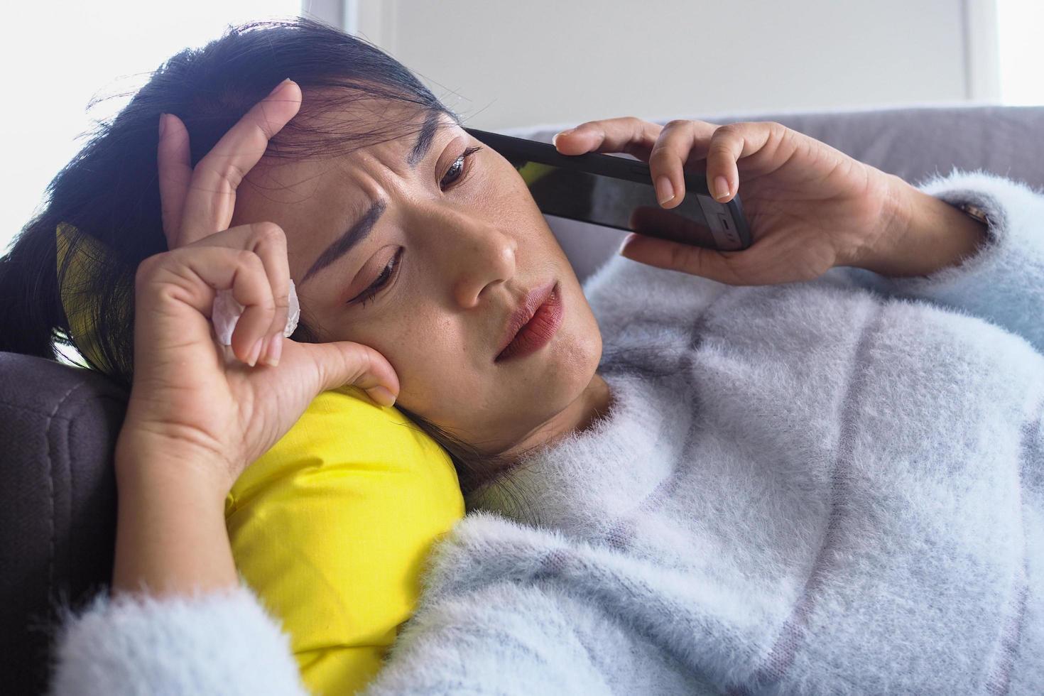 mulher deitada no sofá em casa com expressão facial de ansiedade foto