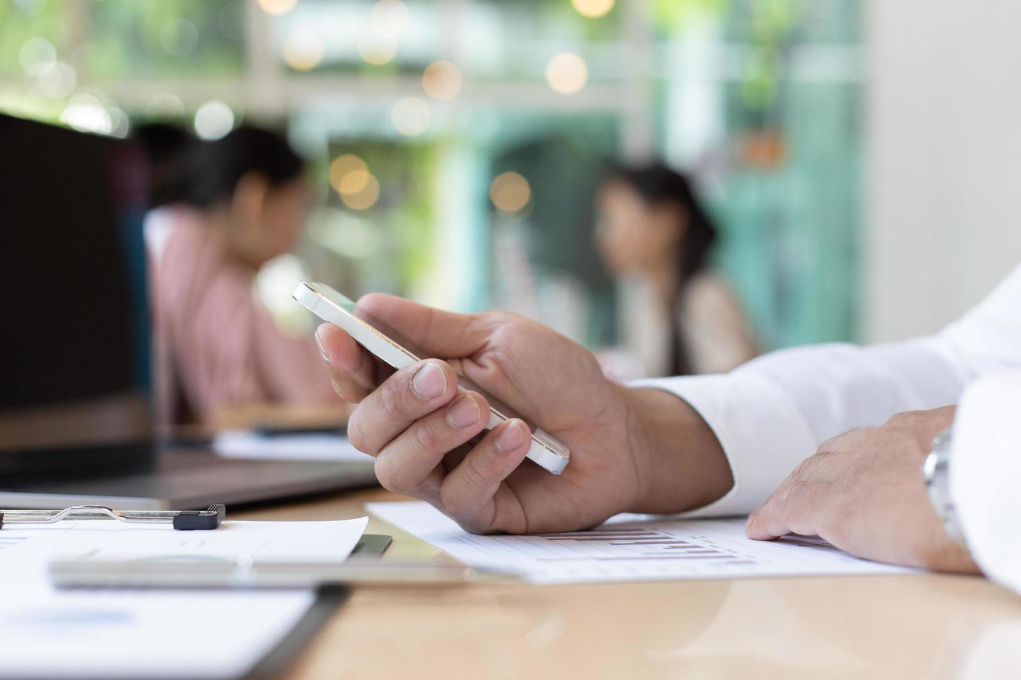 Business person at desk using mobile phone photo