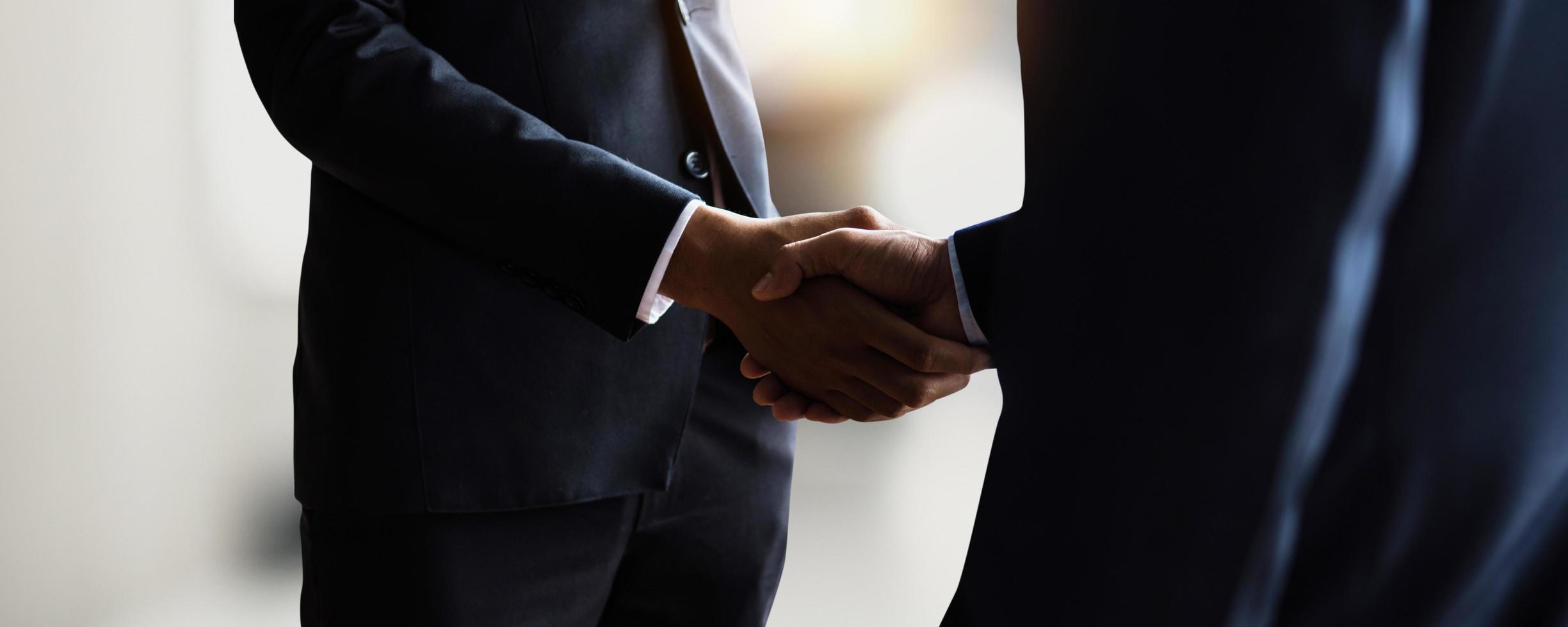 concepto exitoso de negociación y apretón de manos, dos hombres de negocios se dan la mano con el socio para la asociación de celebración y el trabajo en equipo, trato comercial foto