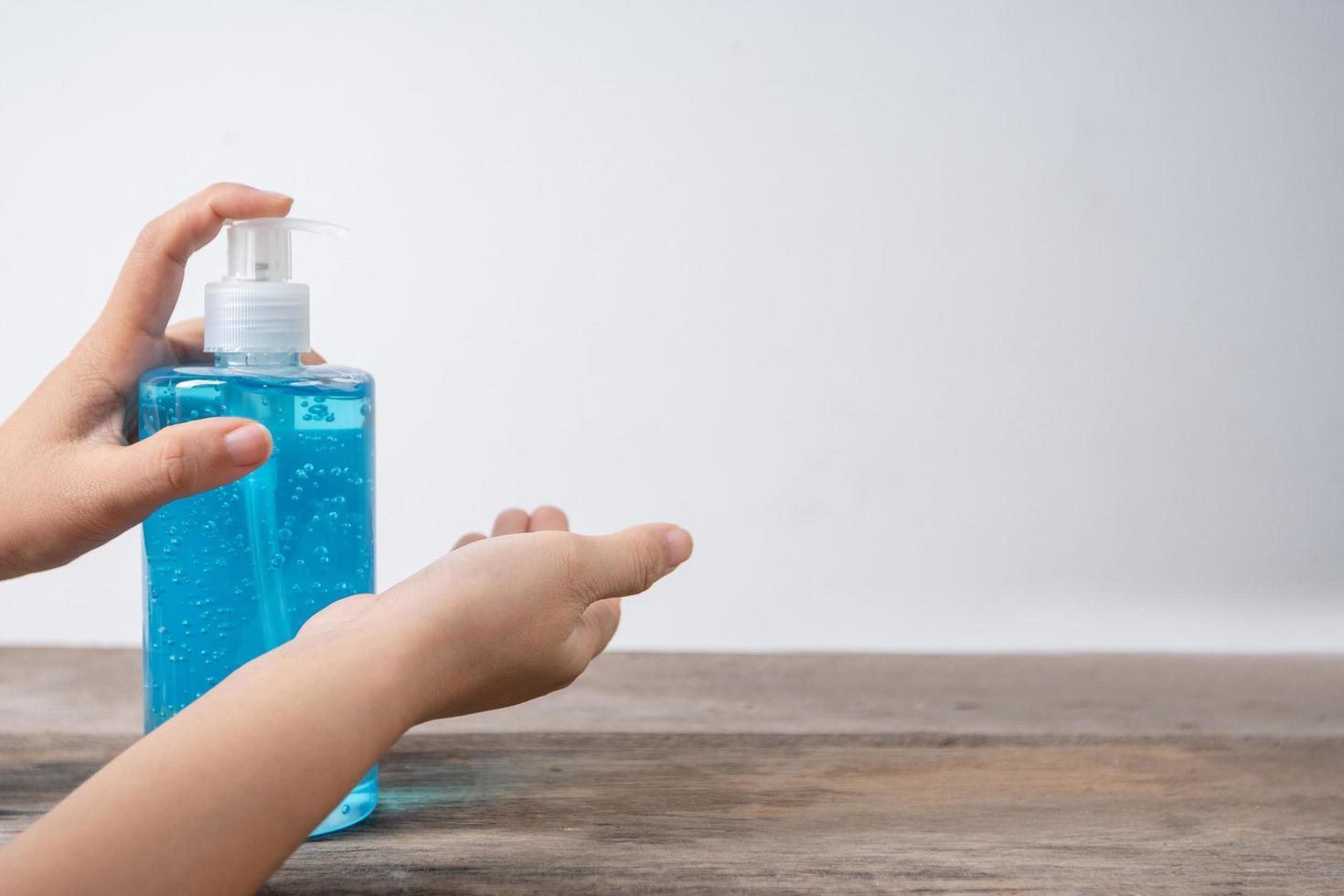 Una mano presionando alcohol desinfectante sobre una mesa foto