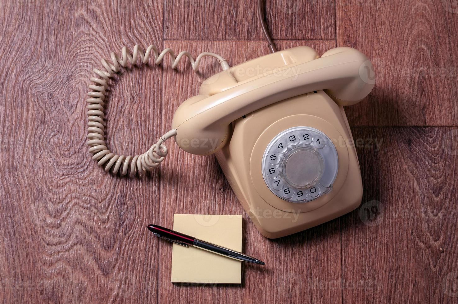 Retro telephone on wooden table in front gradient background photo