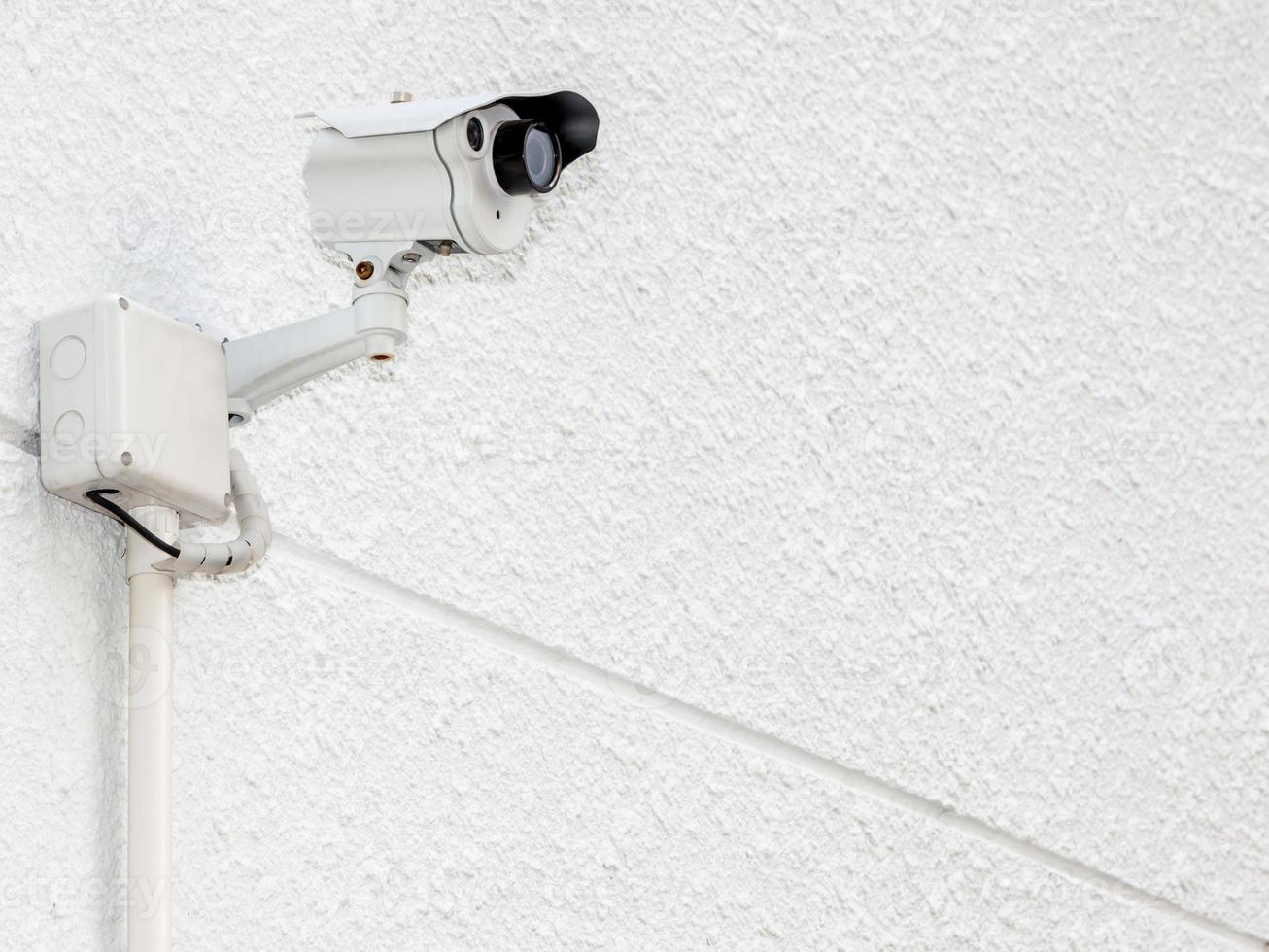 Security camera, CCTV on the white cement wall photo