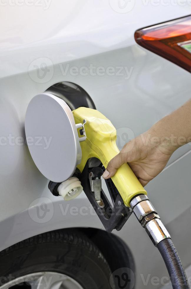 Grey car at gas station being filled with fuel photo