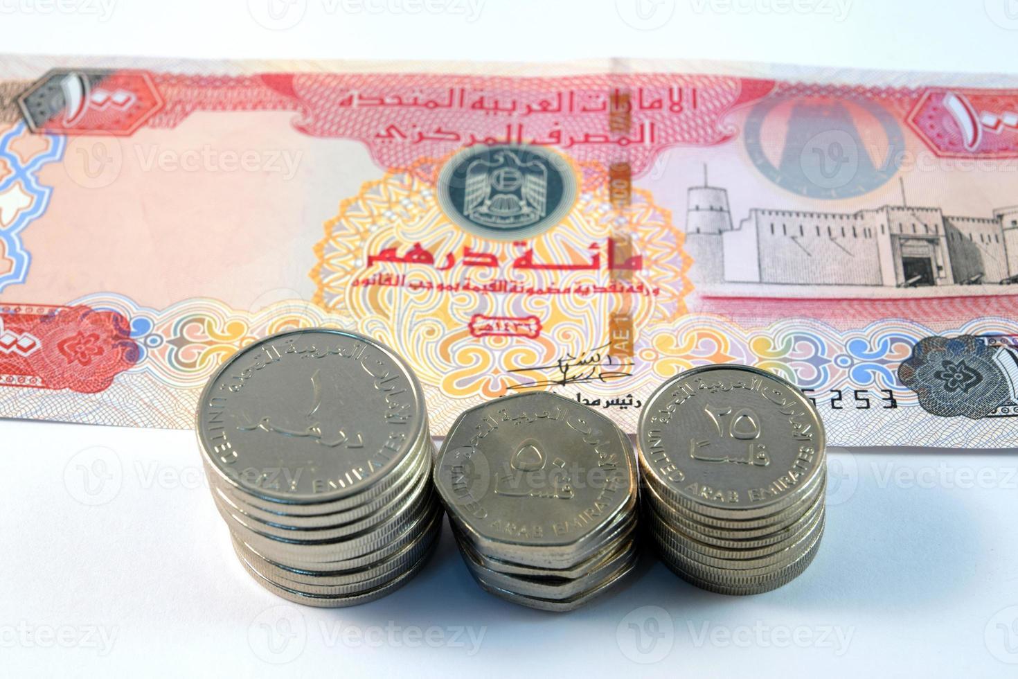 Cerca de varios billetes y monedas de Emiratos Árabes Unidos foto