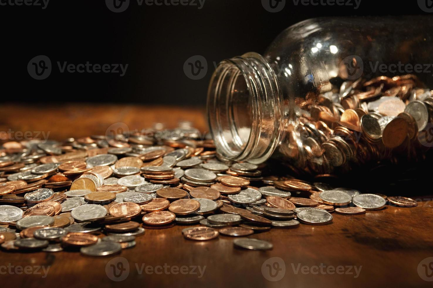 monedas de EE. UU. que se derraman del tarro de cristal grande foto