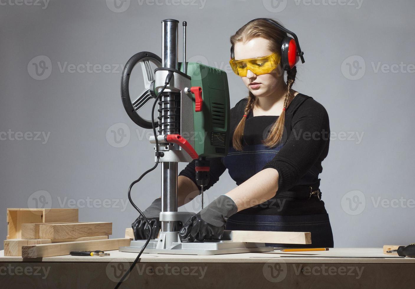 female carpenter and drilling machine. photo