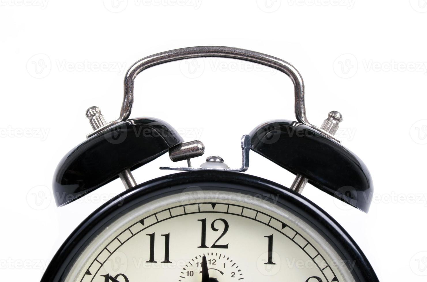 Classic old black alarm clock on white background photo