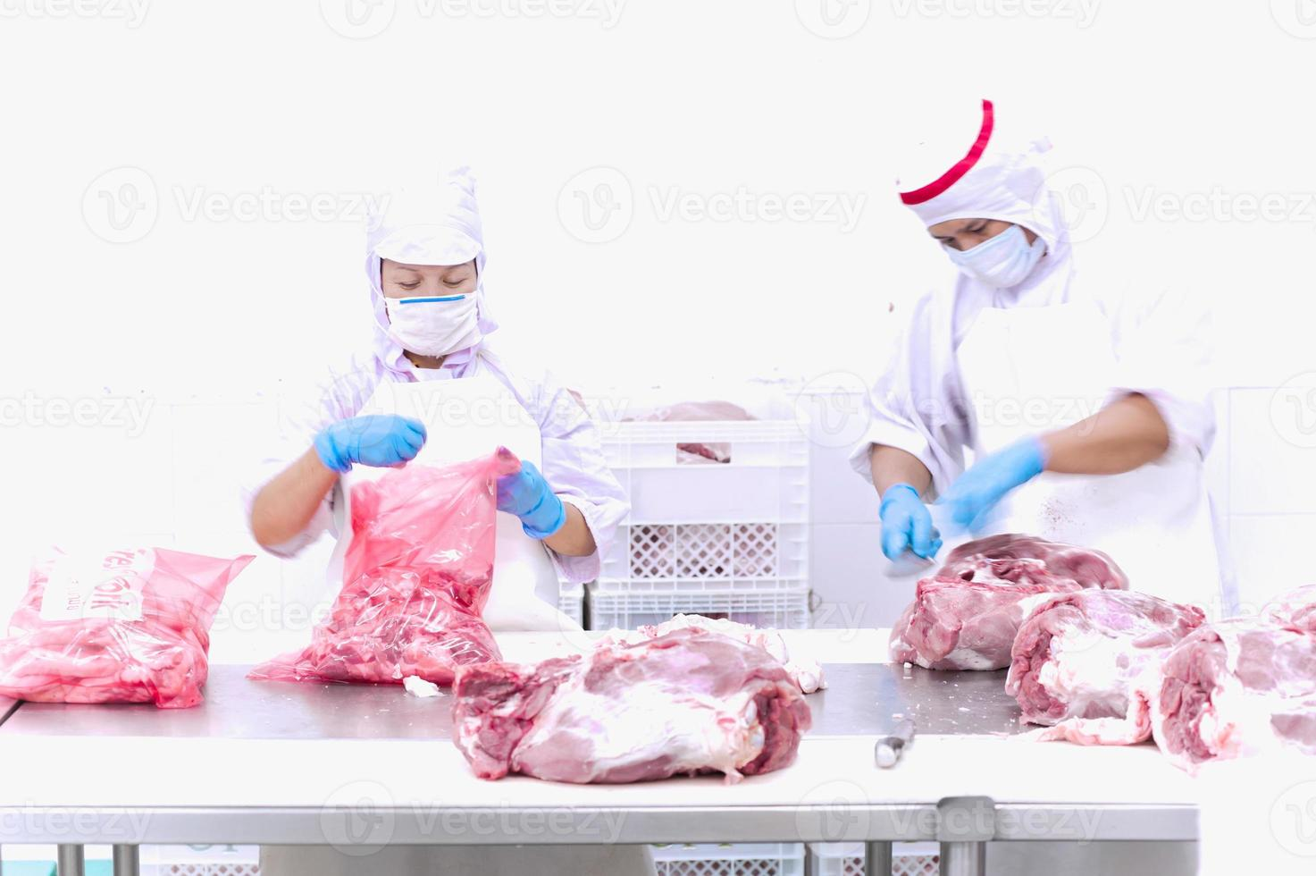 butcher cutting meat on the table photo