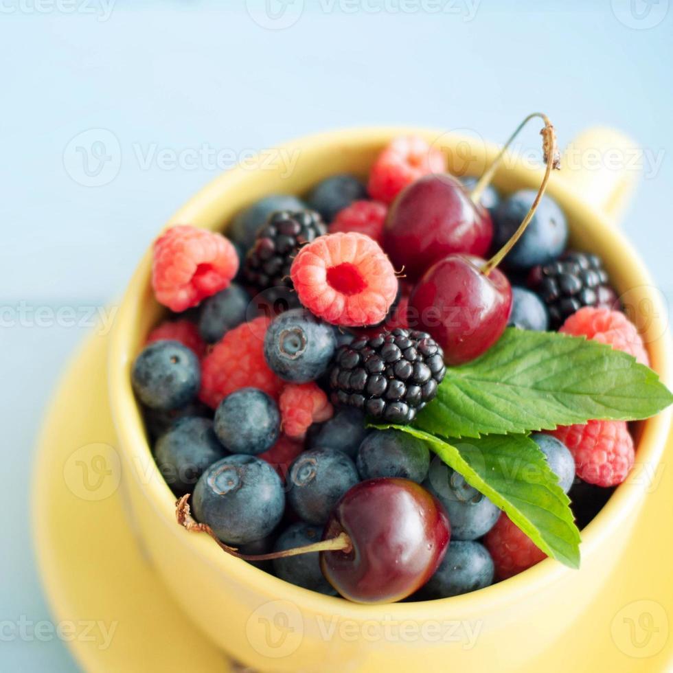 deliciosas bayas frescas sobre fondo de madera azul foto