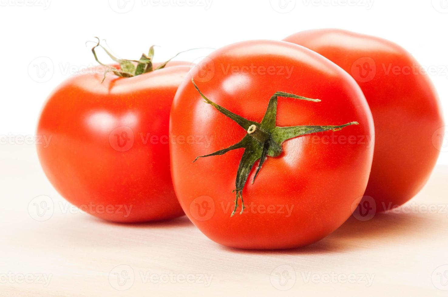 Three perfect red tomatoes on a wooden board photo
