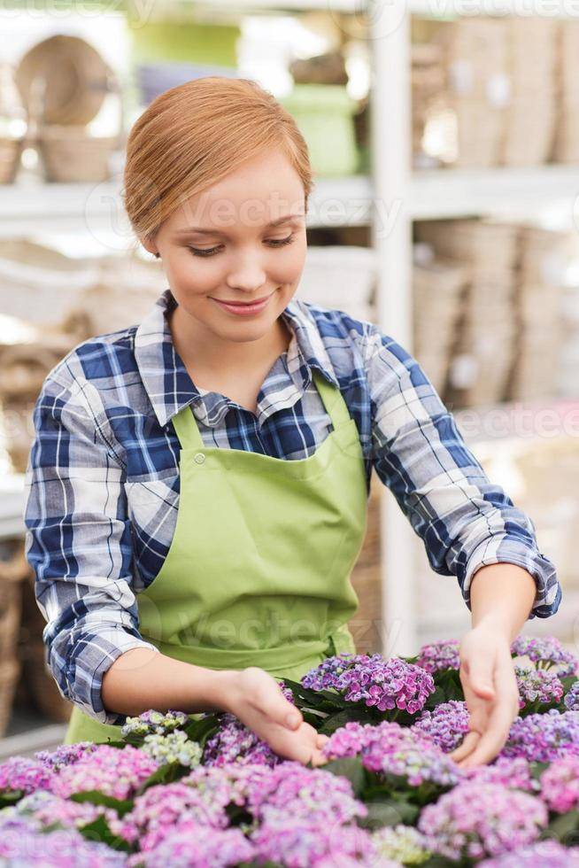 happy woman taking care of flowers in greenhouse photo