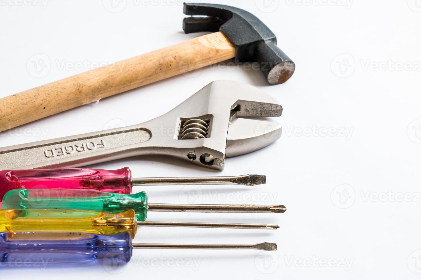 Martillo, destornillador y llave en el fondo blanco. foto