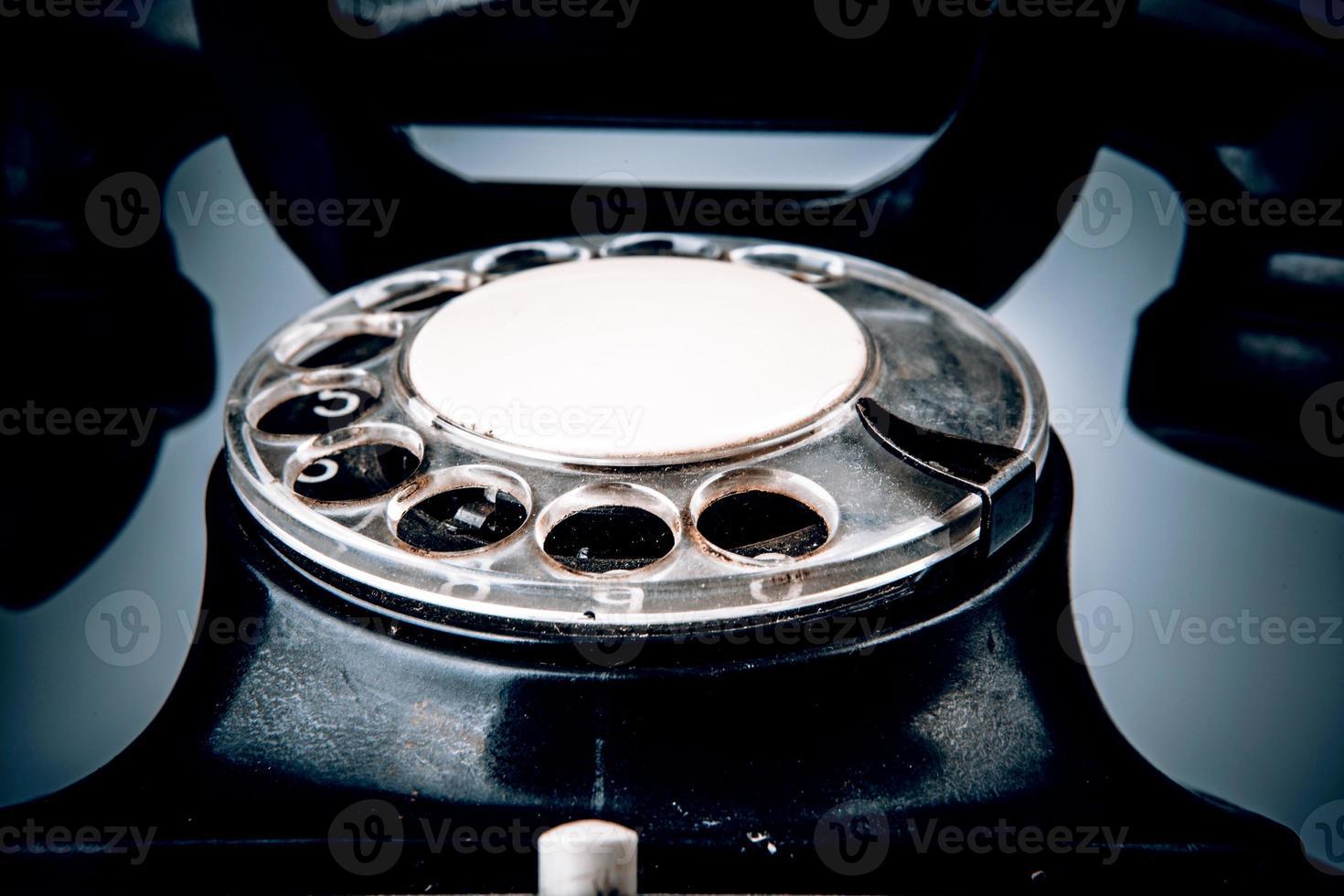 Viejo teléfono negro con polvo y arañazos sobre fondo blanco. foto