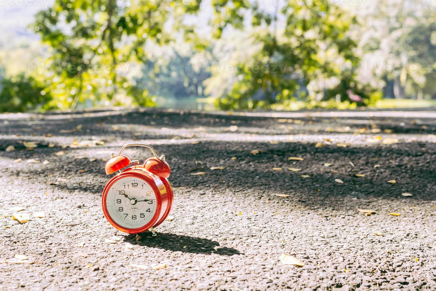 Red alarm clock with two bells on the ground photo