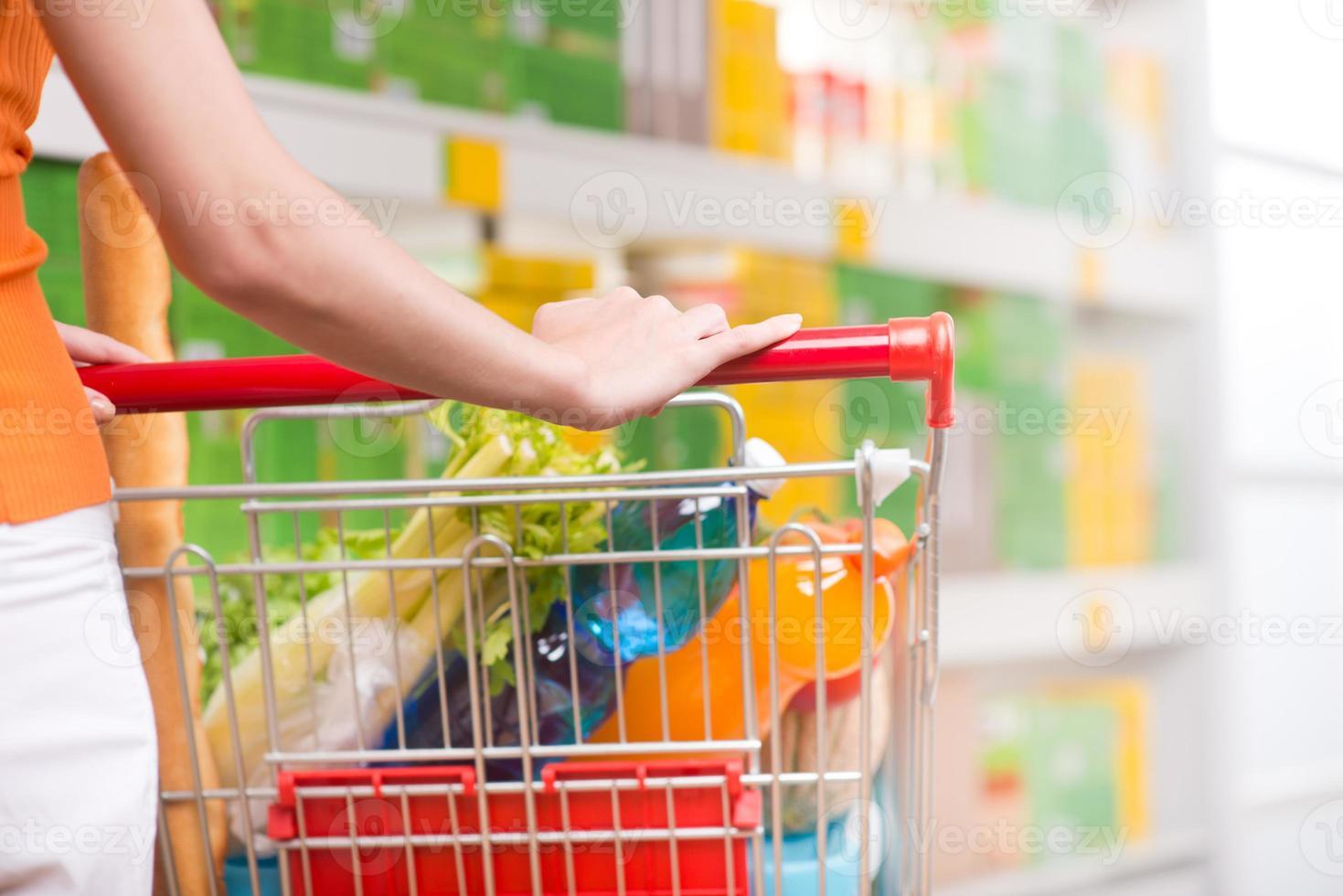 mujer en supermercado con carro foto