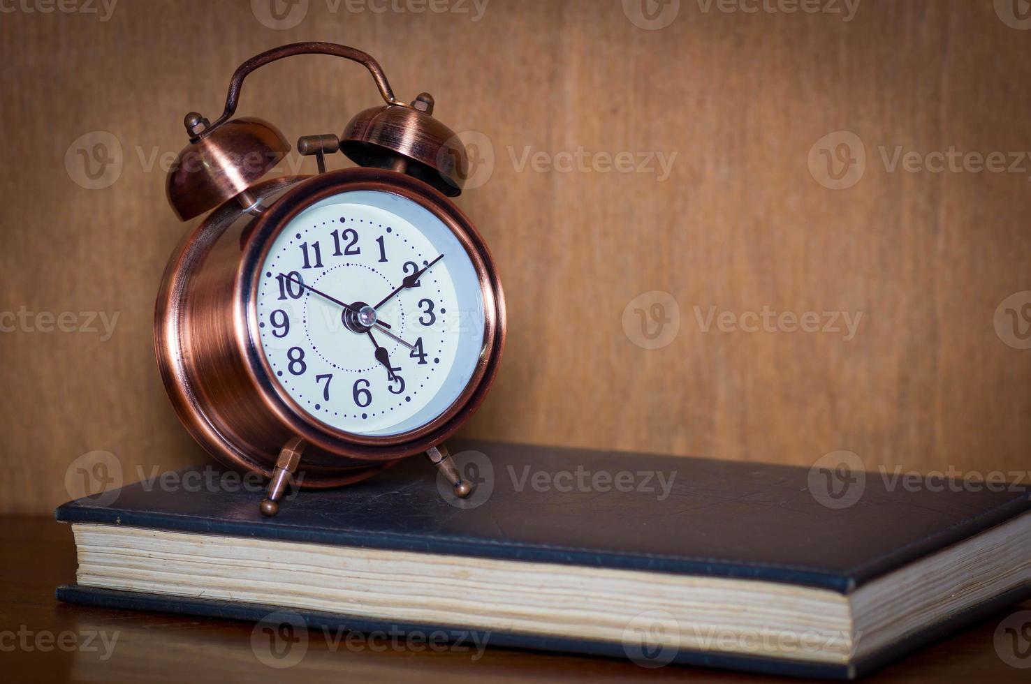 Alarm clock and book. photo