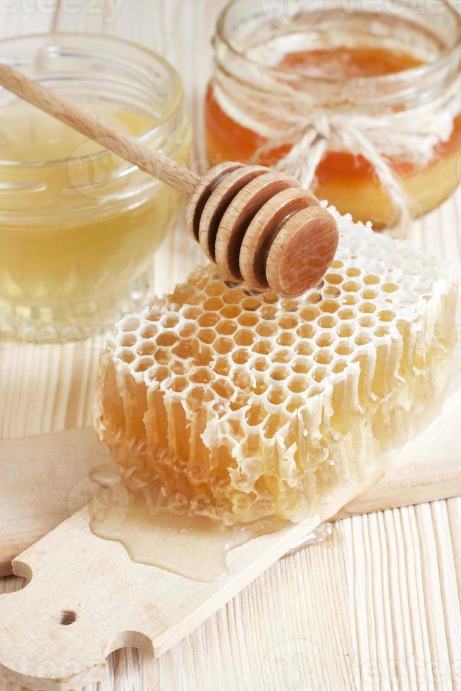miel en tarro con panal y cuchara de madera foto